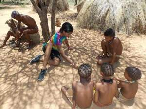 ---Zuriel with the Khoi San people in the Kalahari Deserts, teaching arithmetic figures through play and talk | Credits: Zuriel Oduwole Facebook Page